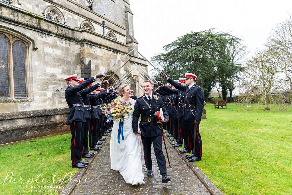 bride and groom walking under sword salute