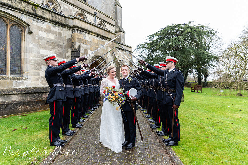 Bride and groom in front of sword arch