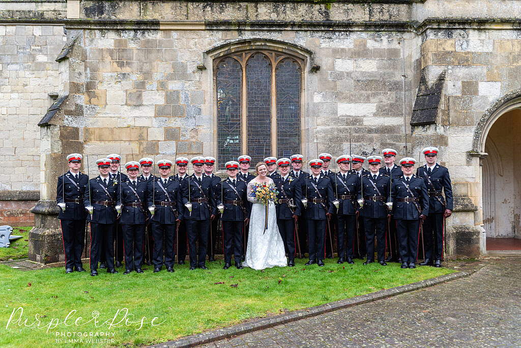 Bride and groom posing with military freinds