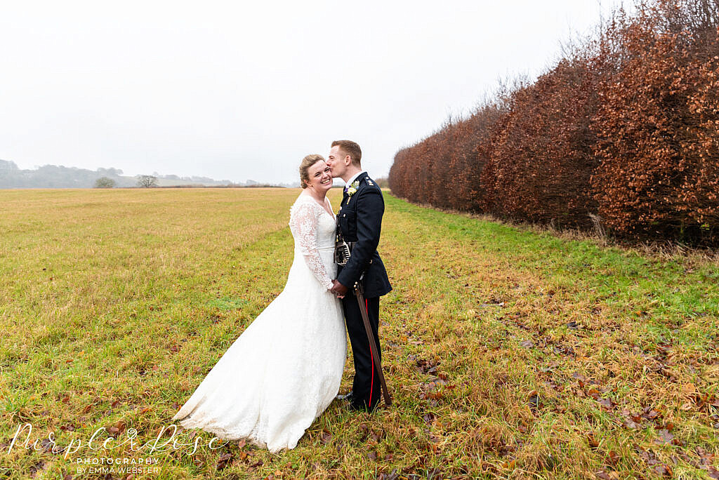Groom kissing his bride in a field