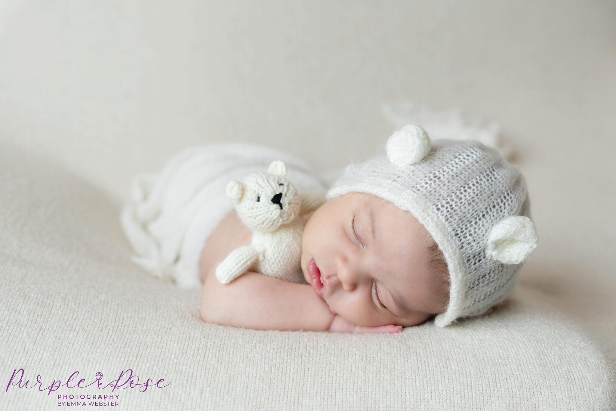 Baby girl cuddling teddy with bear bonnet on