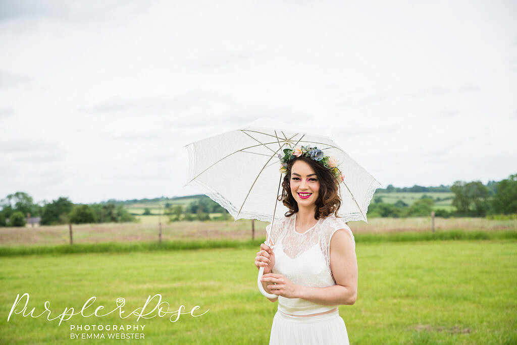 Bride standing under an umbrella