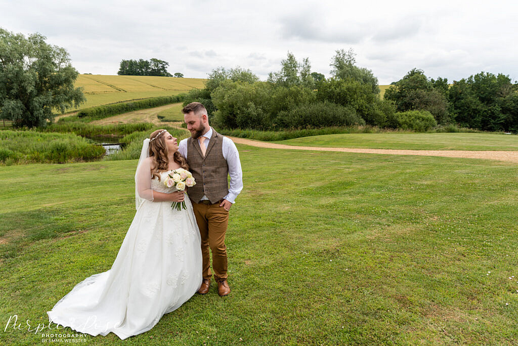 Bride and groom surrounded by countryside
