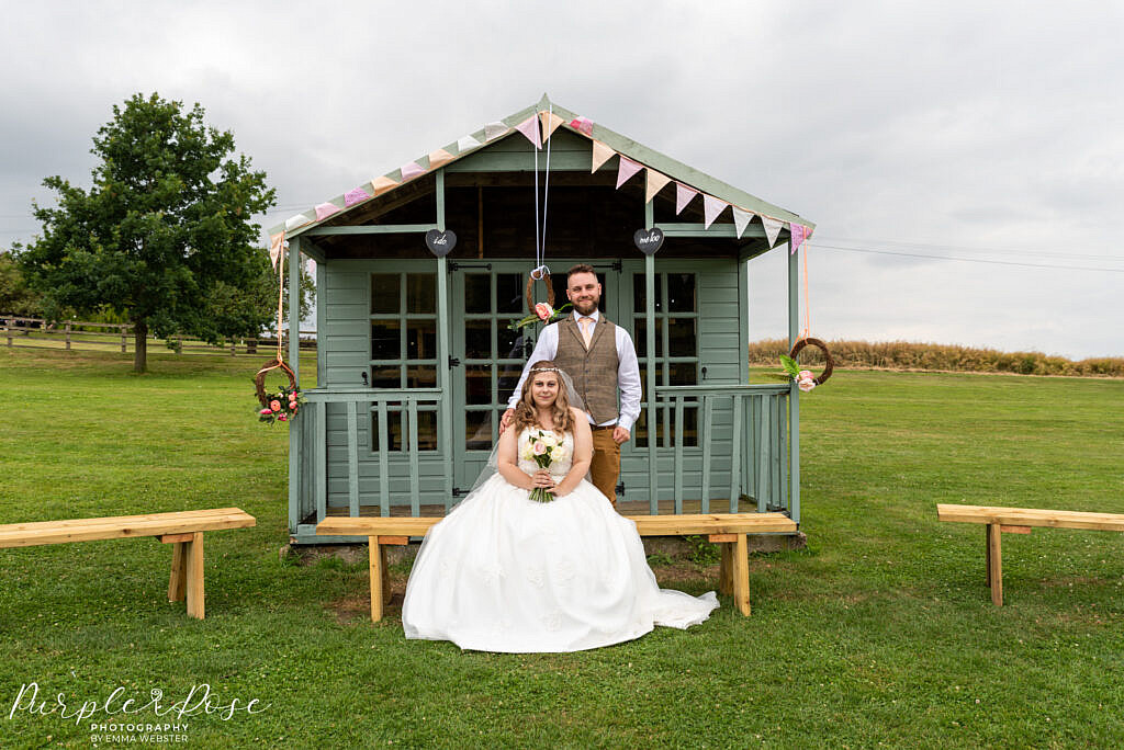 Bride and groom in front of pretty hut