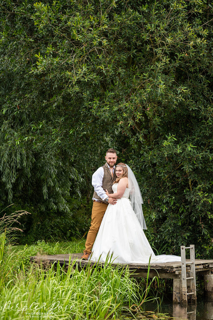 Bride and groom standing together on a fishing platform