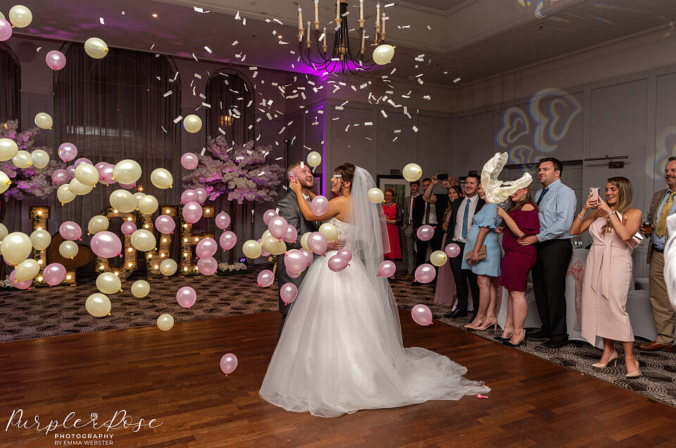 Balloons being dropped during bride and grooms first dance