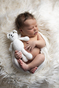 Sleeping baby holding a teddy