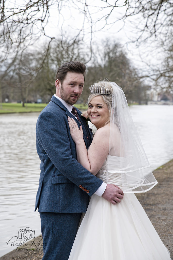 bride and groom standing at Bedford river bank