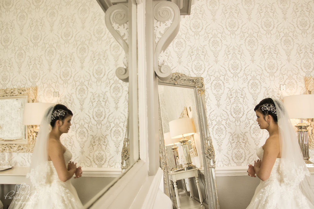 Reflection of a bride checking her reflection in the mirror