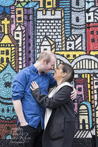 Couple embracing in front of a wall of graffiti