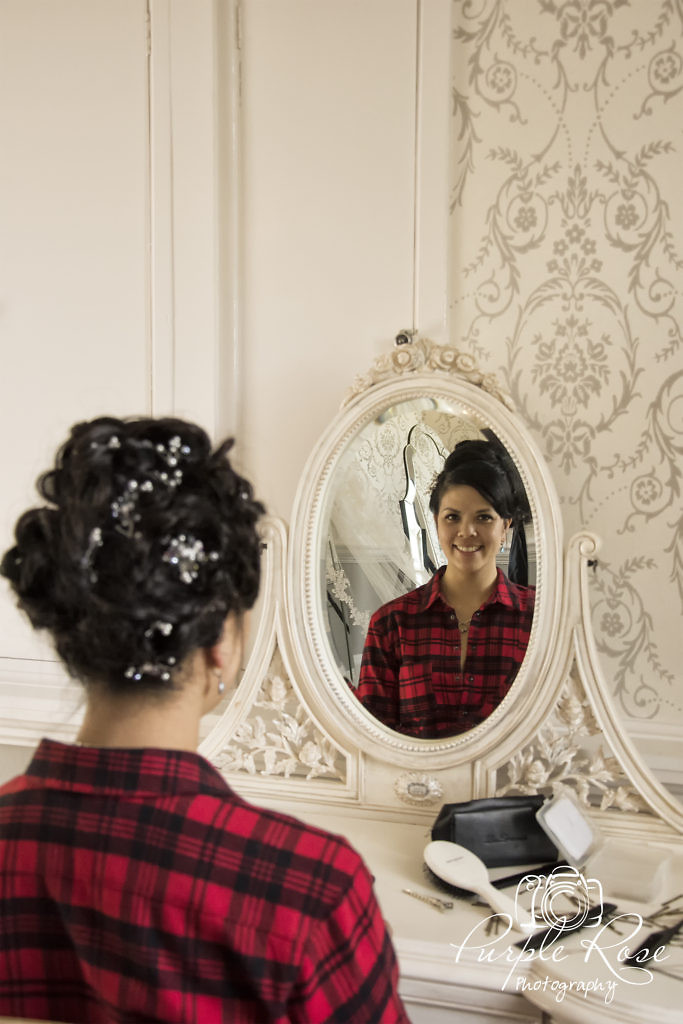 Bride looking into a mirror as she gets ready for her wedding