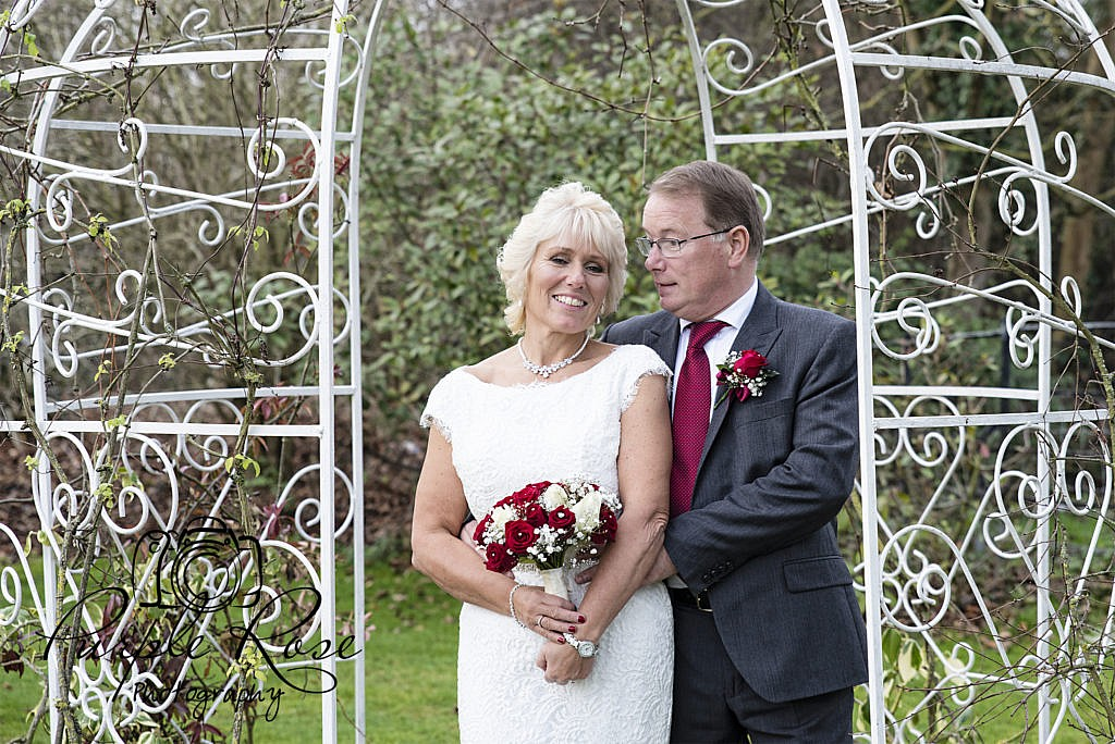 Bride and groom standing together in gardens