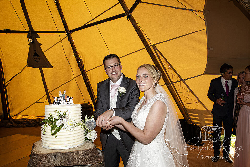 bride and groom cutting their cake in a tipi