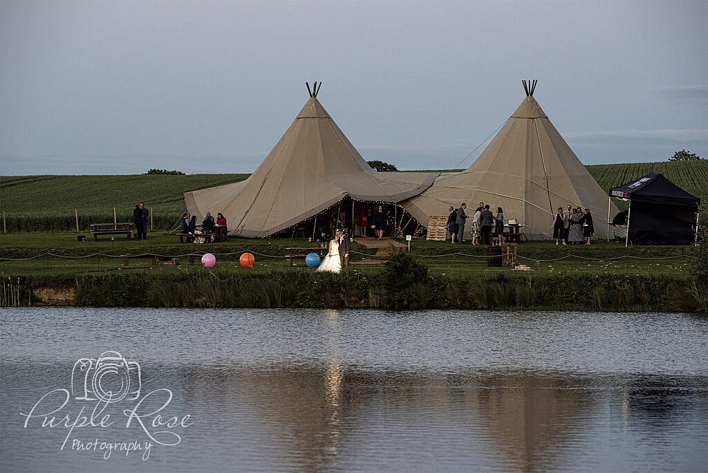 Bride and groom standing in front of tipi's