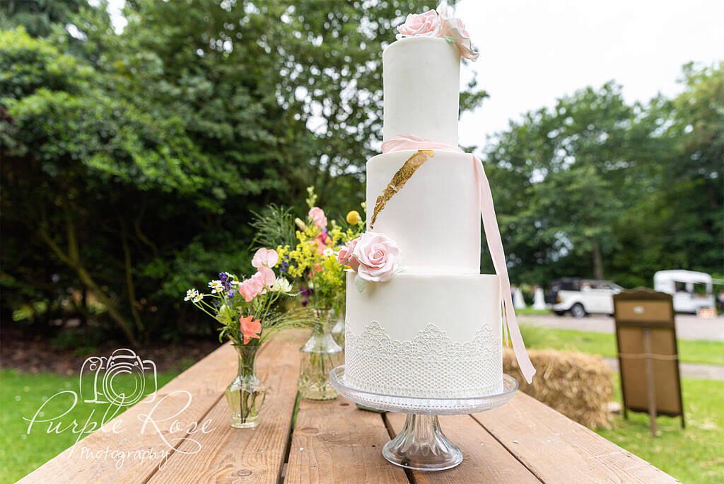 White wedding cake with pink sugar craft roses