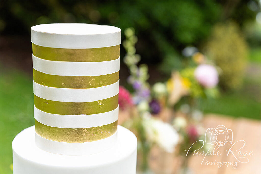 Gold and white striped top of wedding cake