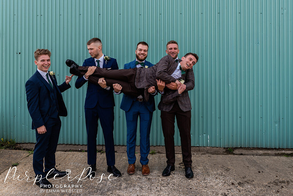 Groomsmen carry the groom
