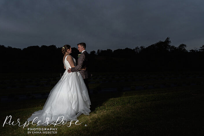 Bride and groom standing together after dark