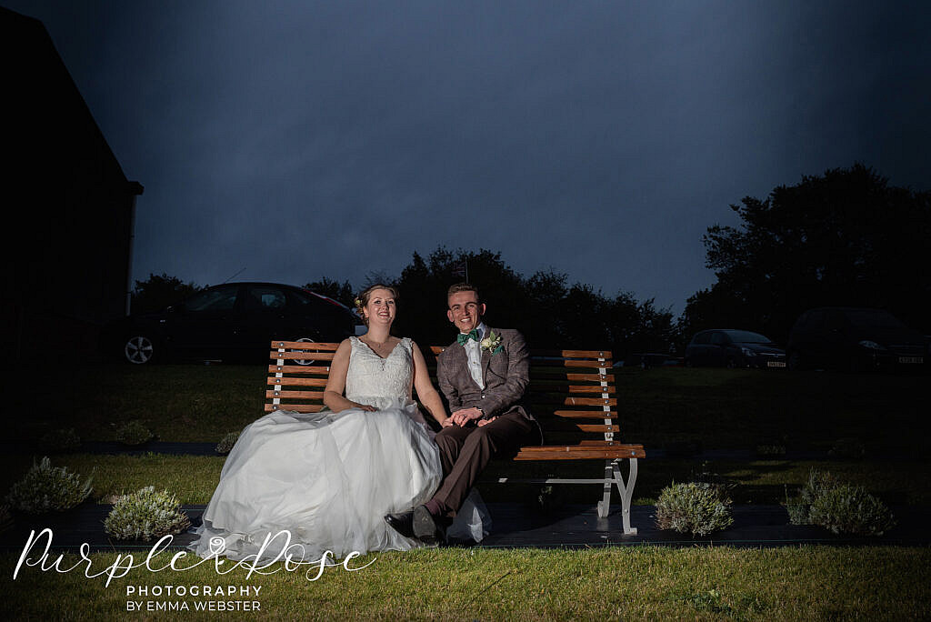 Bride and groom sat on a bench