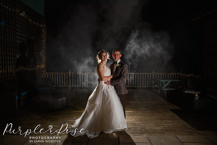 bride and groom with a dark smokey back ground