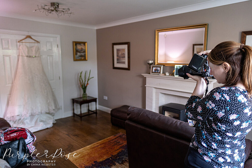 Wedding photographer photographing a wedding dress