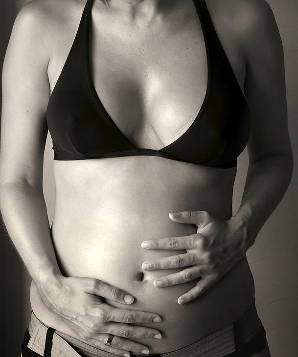 a woman in a sports bra holding her pregnant tummy
