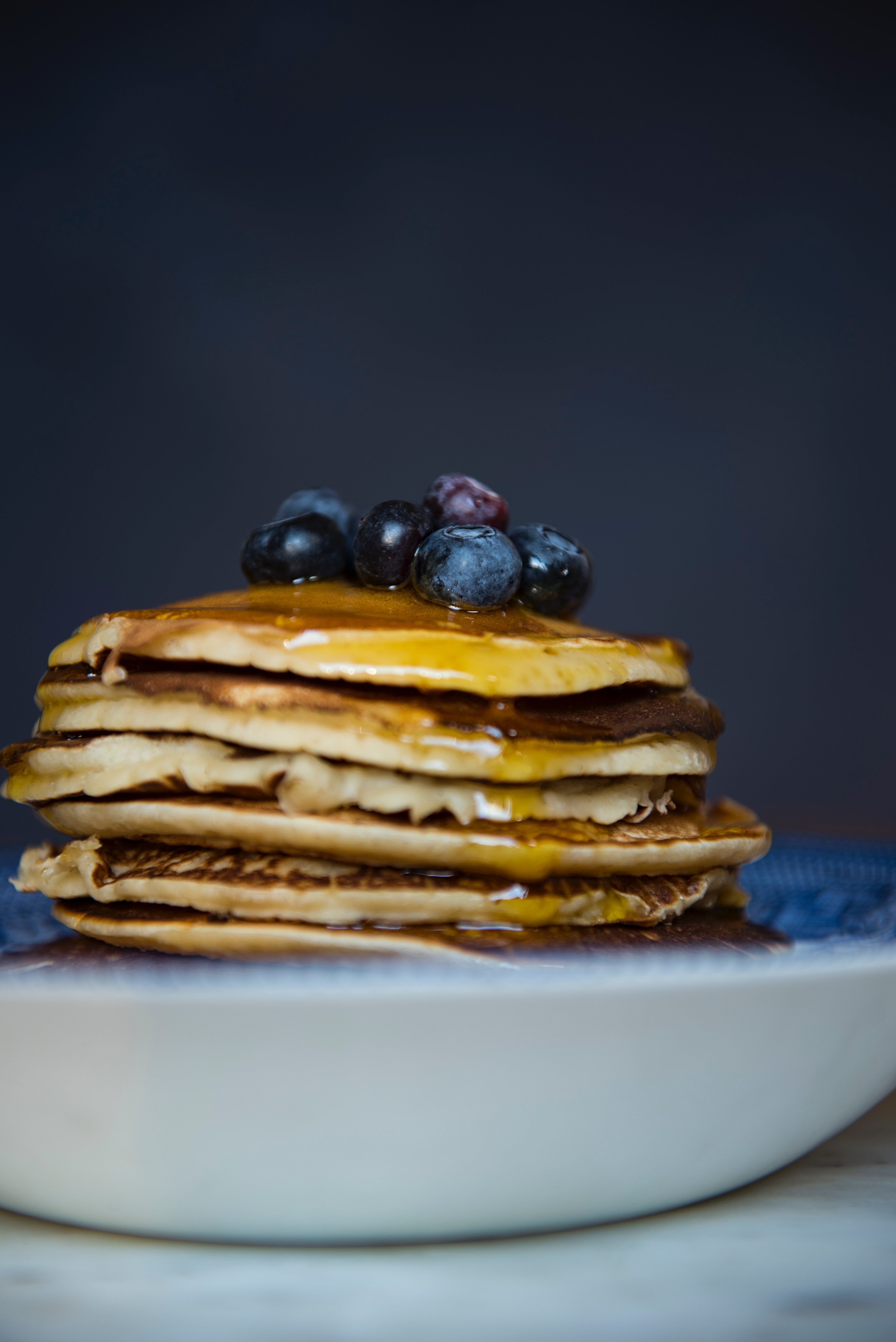 a stack of blueberry pancakes in a bowl with syrup on