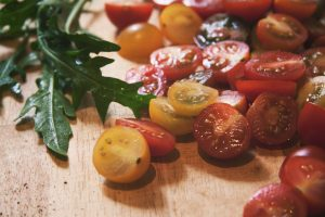 red and yellow tomato halves and rocket on a copping board