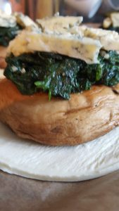 Raw pastry circle with mushroom spinach and stilton on top