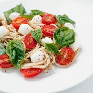 spaghetti with basil leaves halves of baby tomatoes and green basil leaves