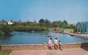 boating lake in a park. people stood eating ice lollies
