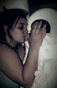 Mummy lying with baby stroking her face