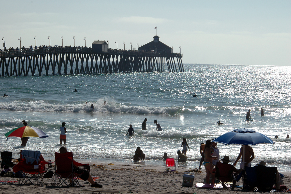 beach with a pier and people in the water