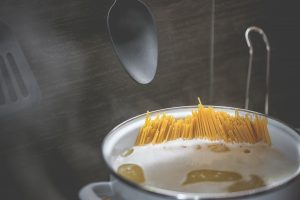 a pot of spaghetti cooking in a saucepan