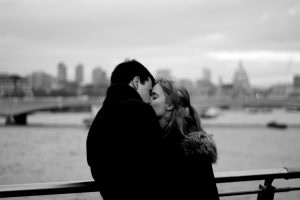 Man and woman in black and white kissing on a bridge