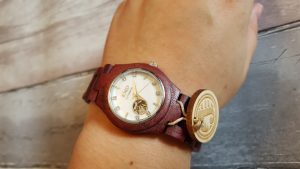 pink/red watch on my wrist with wooden background