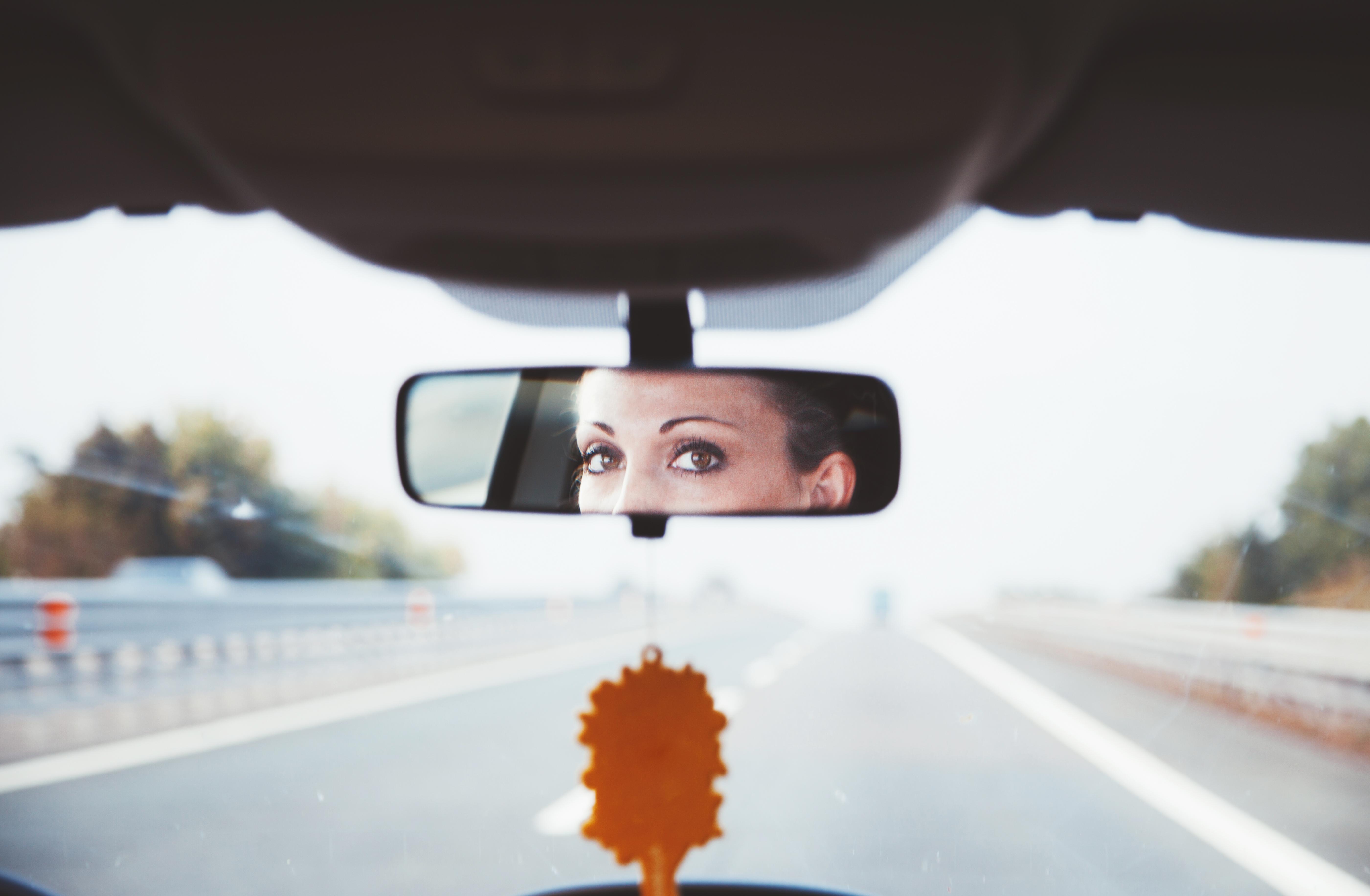 woman looking in rear view mirror