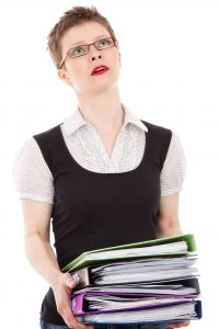 woman stressed holding a lot of files
