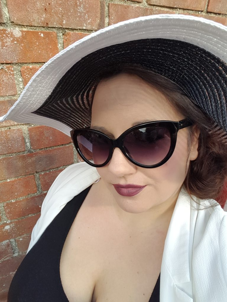 me wearing glasses a big hat and dark lipstick. Red wall in the background