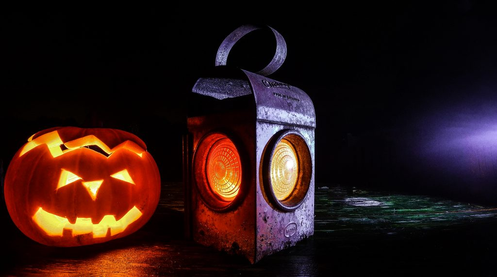 a carved pumpkin lit up with an old style lantern next to it lit too in drkness