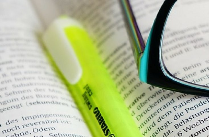 highlighter and glasses in an open book