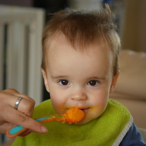 child with a spoon at mouth with orange mush on it