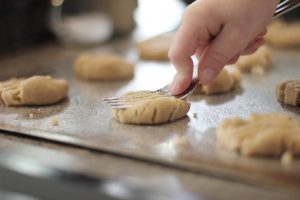 a hand holding a fork pressing down on biscuit dough on a baking tray