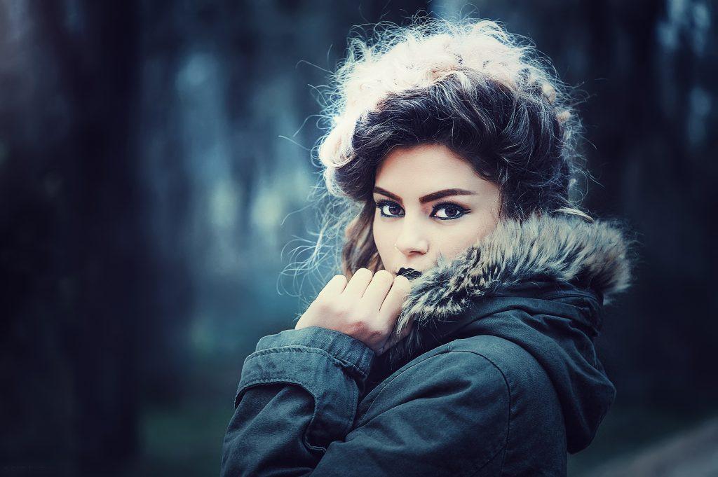 girl in a duffel coat peeking from behind the hood