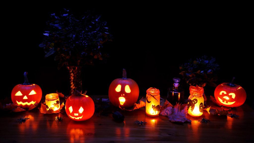 a line of carved pumpkins with different faces all lit