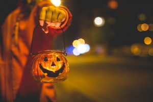 little girls arm holding a tiny glass pumpkin lantern with lights in the background
