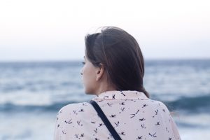 woman looking out at the sea. facing away from the camera