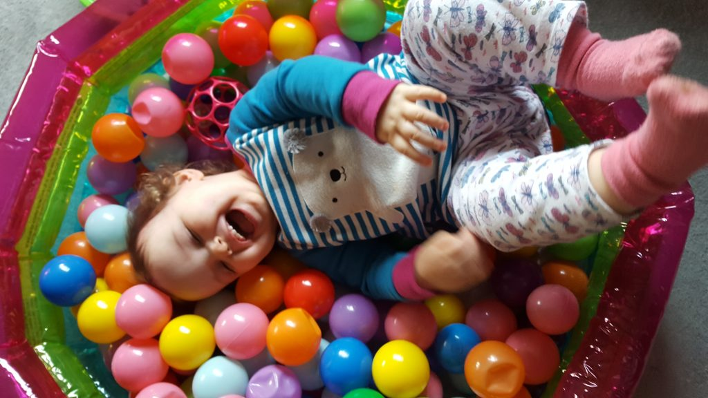 alyssa lying in a ball pit legs in the air