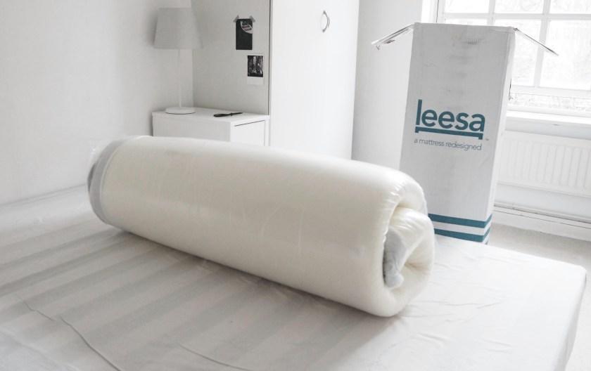 new mattress rolled up next to a box