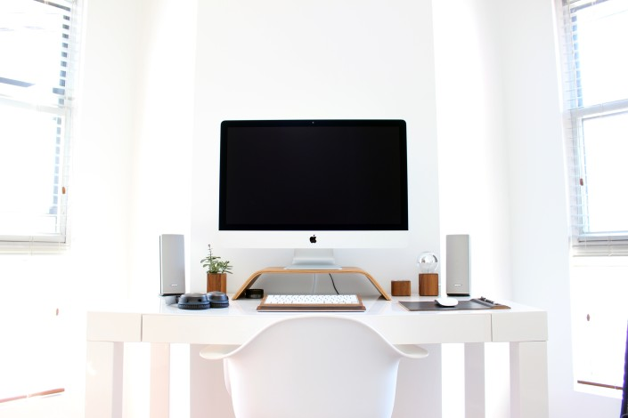 a desk with a computer and speakers on it all white